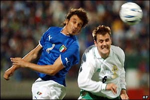 Italy's Massimo Oddo (left) jumps for a header with Northern Ireland's Danny Griffin