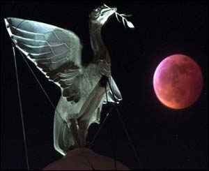 Partially-eclipsed red moon seen adjacent to a Liver Bird atop the Liver Buildings in Liverpool