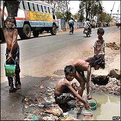 Indian street children fill buckets with water from a puddle on the side of the road in Bhopal