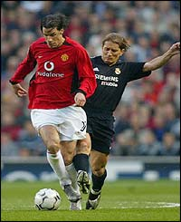 Manchester United's Ruud Van Nistelrooy battles with Real Madrid's Michel Salgado