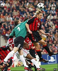 Ajax keeper Bogdan Lobont fights off the Milan attack