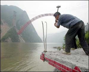 A worker demolishes a lighthouse before it is submerged by the rising waters