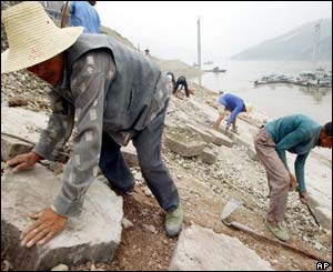 Workers build a stone embankment as water from the Yangtze River rises up the shoreline at the newly built town of Fengjie