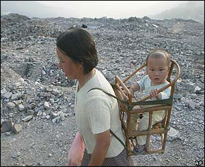 A woman carries a baby through the rubble of the demolished old town of Fengjie