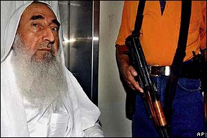 Hamas spiritual leader Sheikh Ahmed Yassin, pictured with armed bodyguard, waits to visit Mr Rantissi