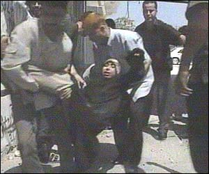Young Palestinian is carried from scene of the attack by residents