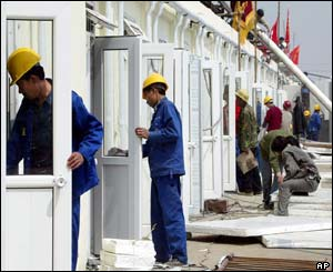 Chinese workers put together prefabricated buildings