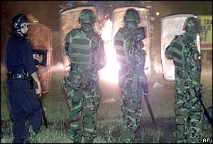 Gendarmerie officers watch burning bins during the riots