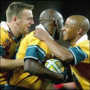Chris Latham and Australian captain George Gregan congratulate Sailor after he scores the second try