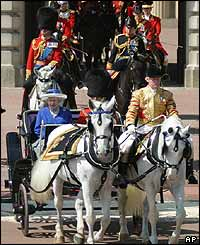 The Queen rides in an open carriage pulled by two greys