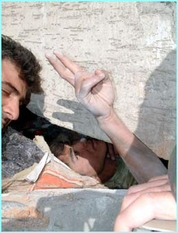 A student trapped in rubble gives the peace sign. The quake measured 6.4 on the Richter scale
