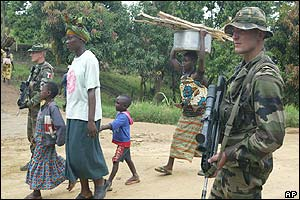 French soldier stands guard as family walks past in Bunia