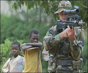 French soldier aims his gun as two children look on in Bunia