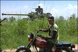Fighter from Union of Congolese Patriots (UPC] on motorbike passes tank