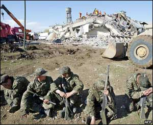Exhausted Turkish soldiers rest in front of the ruins of the school
