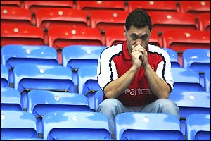 An Arsenal fan sits dejected after the 2-2 draw at Bolton