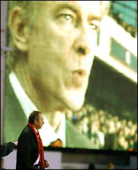 Gerard Houllier is overshadowed by the image of Arsene Wenger on the big screen