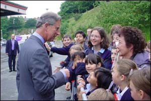 Prince Charles, who is accompanying his son, chats to well-wishers outside the station