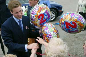 Birthday balloons are offered to the royal visitor