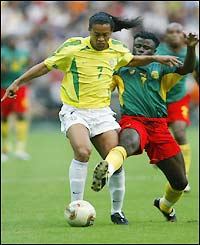 Ronaldinho wrestles the ball from Cameroon's Modeste Mbami