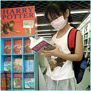 Hong Kong: Lau San Wa, 8, wearing an anti-Sars mask, looks at old Potter book as she waits for the new one to arrive