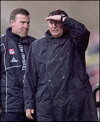 Graham Taylor looks on in the rain as his side lose to Arsenal