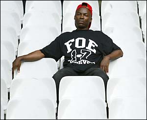 A subduded fan sits in an empty stand wearing a Foe t-shirt