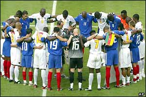 The French and Cameroon players in a circle for the minute's silence