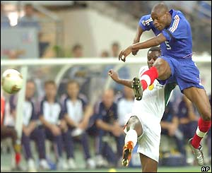 William Gallas volleys the ball ahead of Valery Mezague