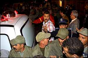 Policemen try to stop people from approaching the Casa de Espana restaurant as an ambulance leaves the place