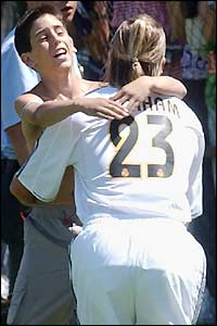 A fan runs onto the training pitch and embraces David Beckham