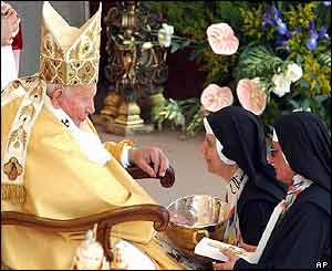 Two nuns present Pope John Paul II with a bowl and crucifix during a solemn Mass to proclaim four new saints