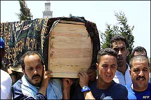 Mourners carry a bomb victim's coffin