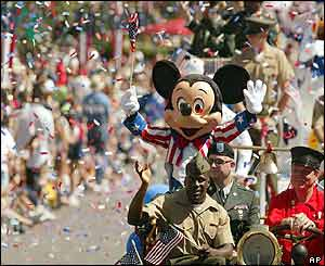A person dressed as Mickey Mouse rides US soldiers during a parade at Disneyland in Anaheim, California
