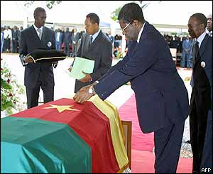 Cameroon' Prime Minister Peter Masany Musonge lays a posthumous medal on Foe's coffin