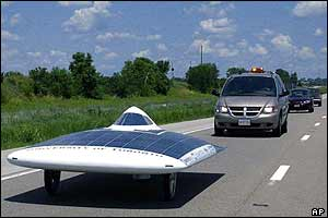 Solar car speeds ahead of regular car on highway
