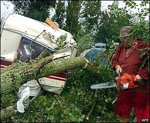 A camper clears his caravan from branches with a chainsaw at the Gennes campsite, central France