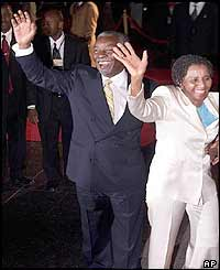 South African President Thabo Mbeki and his wife Zanele wave to well-wishers