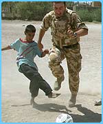 A British soldier plays football with an Iraqi boy