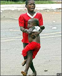 A boy carrying his young brother flees the mortar attack near the US embassy in Monrovia