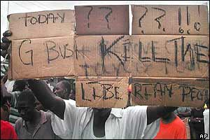 A man carries a placard reading 'Today G Bush kill the Liberian people' near the US embassy