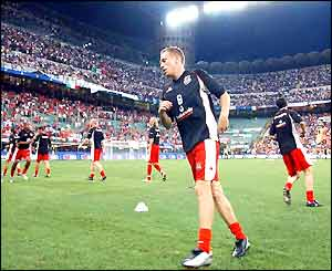 Craig Bellamy warms up with his Welsh team-mates in the San Siro
