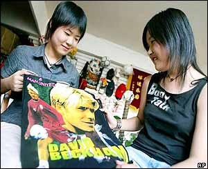 Sixteen-year-old cousins He Yajing and Zhu Keyi look at a shoulder bag with a picture of soccer star David Beckham