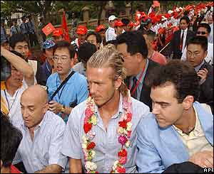 David Beckham is escorted through a cheering crowd as he arrives at Kunming's Hongta Sports centre