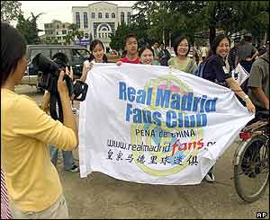 Local fans hold a banner to welcome the arrival of the members of Real Madrid outside Kunming International Airport