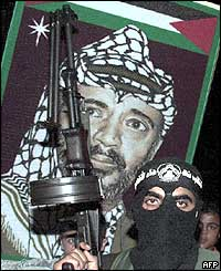 Palestinian gunman in front of a portrait of Yasser Arafat at a demonstration in Gaza City