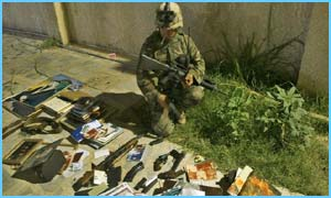 A US soldier inspects items seized in a raid in which a man suspected of being Saddam's bodyguard was seized