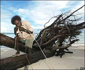A man uses his teeth to split vines in order to make rope on Kennedy Island