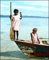 Children use an old timber canoe to reach the shores of Kennedy Island