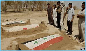 Iraqi men stand after praying at the graves of Saddam Hussein's sons